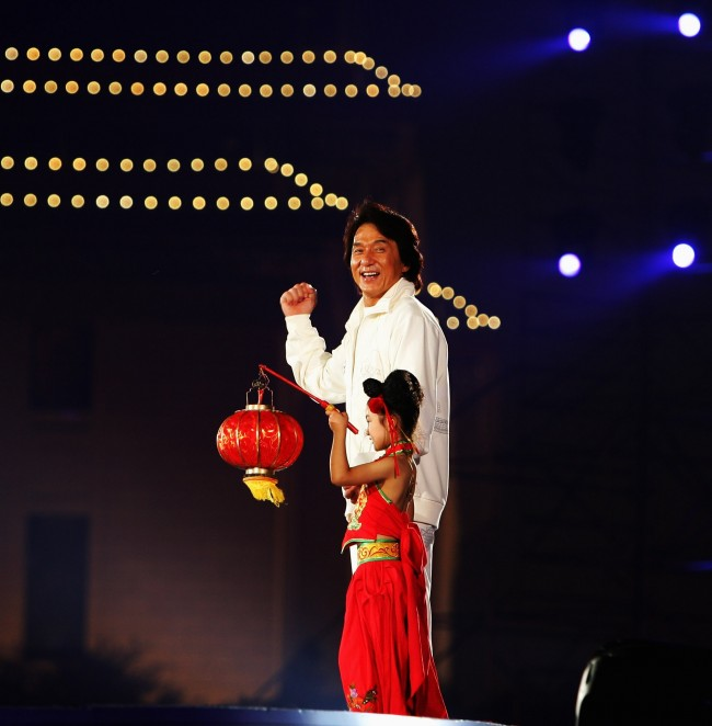 Caption:BEIJING - AUGUST 08: Hong Kong actor Jackie Chan walks onstage with a little girl during a ceremony to mark one year countdown to the Olympics at Tiananmen Square on August 8, 2007 in Beijing, China. Various events are being held in the Chinese capital to celebrate the one-year countdown to the opening ceremony of the 2008 Olympic Games today. (Photo by Guang Niu/Getty Images)