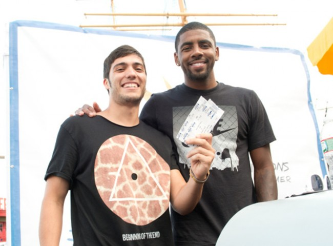 NEW YORK, NY - AUGUST 21: NBA player Kyrie Irving (R) gives a fan tickets for the upcoming USA Basketball team game at The Summer Of Jeep at South Street Seaport on August 21, 2014 in New York City