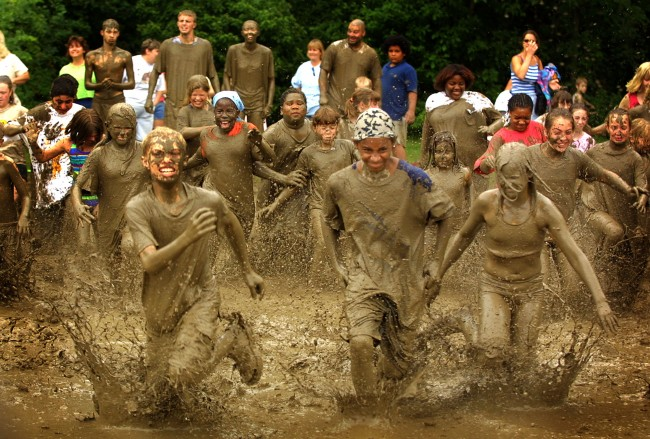 Caption:WESTLAND, MI - JULY 9: Hundreds of children participate in a relay race in a giant mud hole during Wayne County's Annual Mud Day July 9, 2002 in Westland, Michigan. The Wayne County parks department mixed 200 tons of topsoil and 20,000 gallons of water and created a giant mud hole for children ages 12 and under to play in. (Photo by Bill Pugliano/Getty Images)