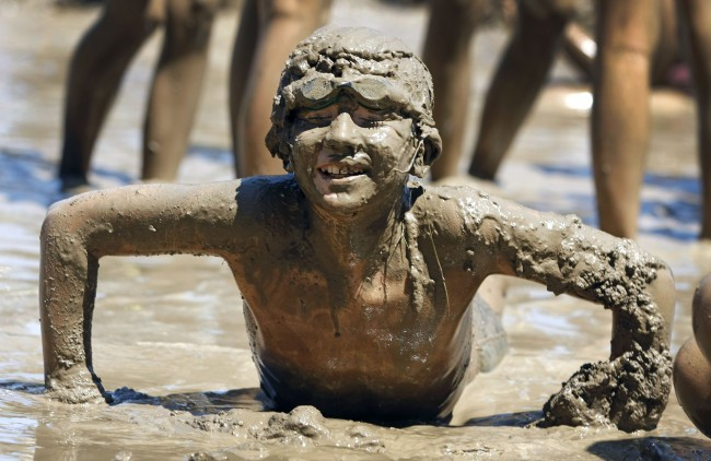 Caption:WESTLAND, MI, - JULY 10: Ben Rojewski, age 11, of Livonia, Michigan rises from the mud while playing in a giant lake of mud at the 25th annual 'Mud Day' July 10, 2012 in Westland, Michigan. The event, which features a 75' by 150' pit filled with 20,000 gallons of water and 200 tons of topsoil, draws about a thousand children each year. (photo by Bill Pugliano/Getty Images)