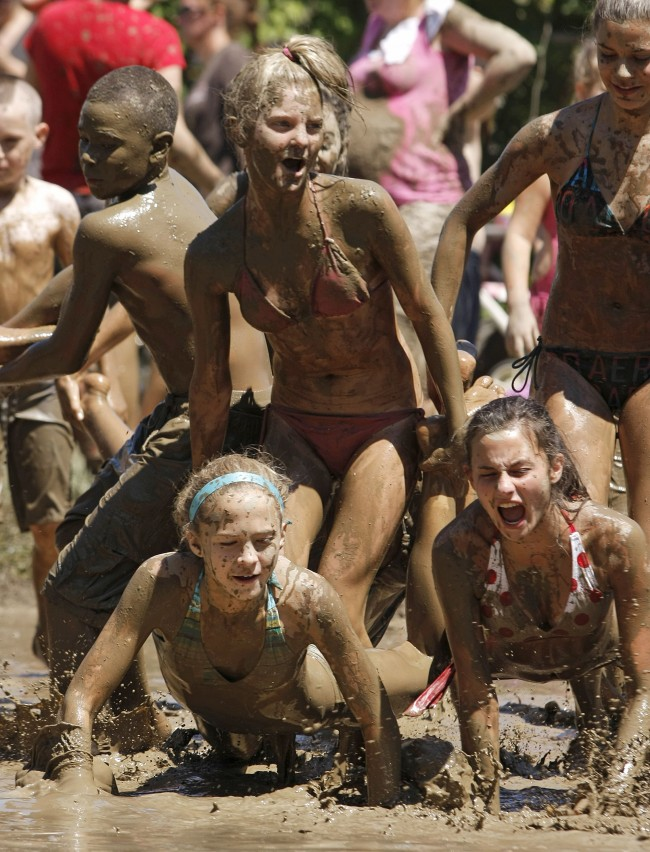 Caption:WESTLAND, MI, - JULY 10: Kids play in a giant lake of mud at the 25th annual 'Mud Day' July 10, 2012 in Westland, Michigan. The event, which features a 75' by 150' pit filled with 20,000 gallons of water and 200 tons of topsoil, draws about a thousand children each year. (photo by Bill Pugliano/Getty Images)