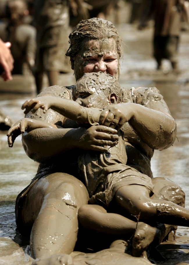 Caption:Westland, MI - JUNE 27: Jodi Reed of Westland, Michigan plays with her three-year old daughter Victoria in a giant lake of mud during Mud Day at Nankin Park July 10, 2007 in Westland, Michigan. The annual Mud Day event consists of 200 tons of topsoil combined with 20,000 gallons of water and is sponsored by the Wayne County parks and recreation department. (Bill Pugliano/Getty Images)