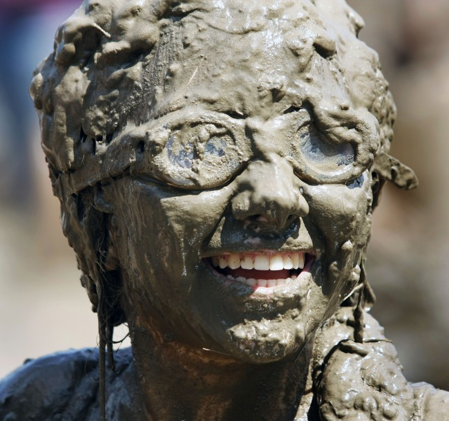 Caption:WESTLAND, MI - JULY 12: A girl smiles while covered in mud during Wayne County's 2011 Mud Day event at Nankin Mills Park July 12, 2011 in Westland, Michigan. The annual event consists of 20,000 gallons of water mixed with 200 tons of topsoil. (Photo by Bill Pugliano/Getty Images)