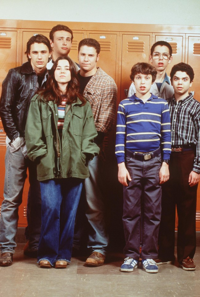 The cast of 'Freaks And Geeks.' From l-r: James Franco (as Daniel), Linda Cardellini (as Lindsay Weir, front, green jacket), Seth Rogen (as Ken Miller, plaid shirt), John Daley (as Sam Weir, front blue striped shirt), Martin Starr (as Bill Havenchuck, back wearing glasses) and Samm Levine (as Neal, far right).