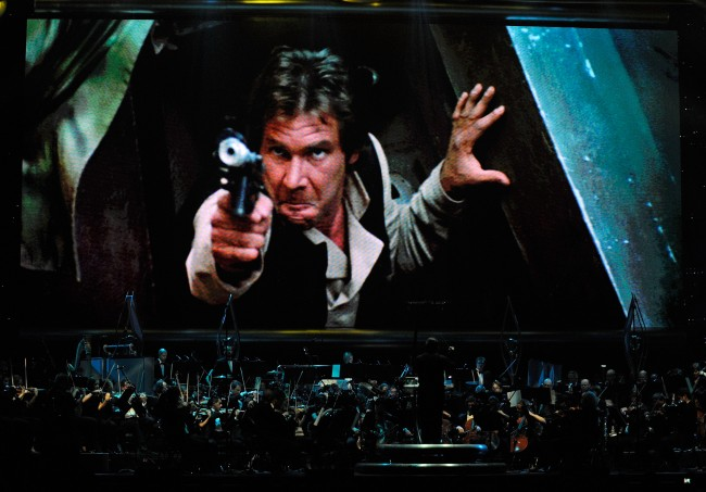 LAS VEGAS - MAY 29: Actor Harrison Ford's Han Solo character from 'Star Wars Episode VI: Return of the Jedi' is shown on screen while musicians perform during 'Star Wars: In Concert' at the Orleans Arena May 29, 2010 in Las Vegas, Nevada. The traveling production features a full symphony orchestra and choir playing music from all six of John Williams' Star Wars scores synchronized with footage from the films displayed on a three-story-tall, HD LED screen.