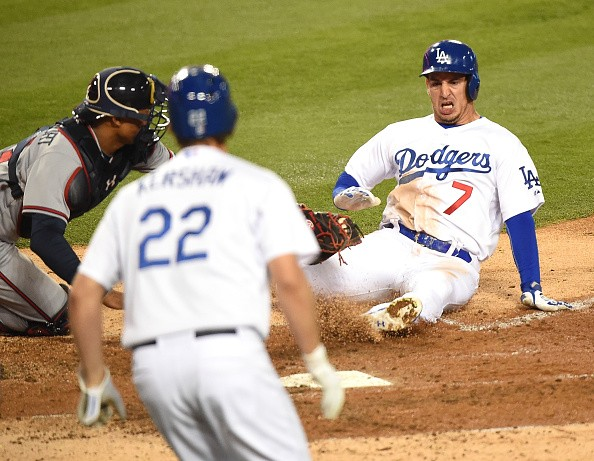 Alex Guerrero #7 of the Los Angeles Dodgers is tagged out by Christian Bethancourt #27 of the Atlanta Braves as Clayton Kershaw #22 watches during the fourth inning at Dodger Stadium on May 26, 2015 in Los Angeles, California.