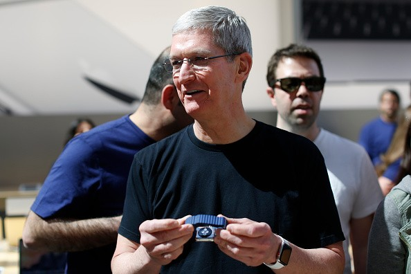 Apple CEO Tim Cook holds an Apple Watch at an Apple Store on April 10, 2015 in Palo Alto, California. The pre-orders of the highly-anticipated wearable from the tech giant begin today as the watches arrive at stores for customers to preview.