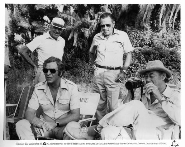 Richard Fleischer, Michael Caine, William Holden, and Rex Harrison sitting off-camera from the film 'Ashanti', 1979.