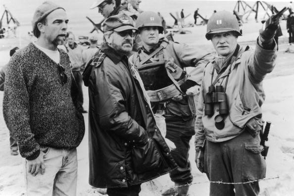 Director Steven Spielberg and actor Tom Hanks listen as an unidentified man points with a walkie-talkie on the set of the film, 'Saving Private Ryan,' 1998