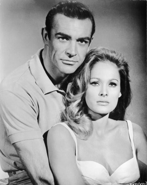 Scottish actor Sean Connery, as fictional secret agent James Bond, and Swiss actress Ursula Andress pose together in a promotional still for the film 'Dr. No,' directed by Terence Young, 1962.