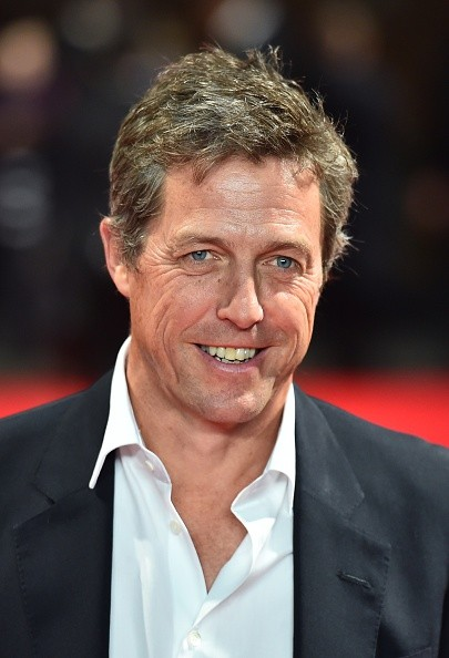 British actor Hugh Grant poses for pictures on the red carpet as he arrives to attend the European premier of his latest film 'The Rewrite' in London on October 7, 2014