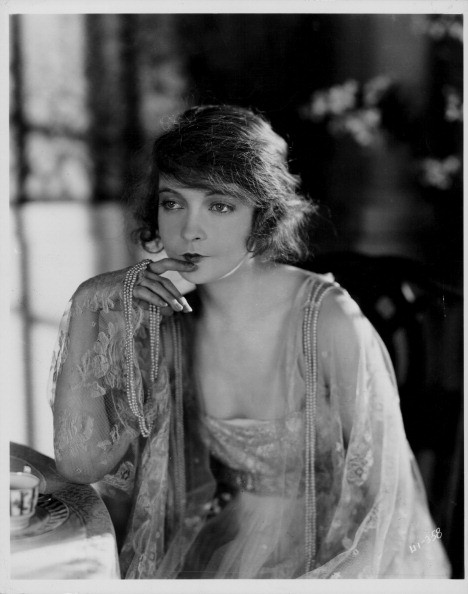 Portrait of actress Lillian Gish holding a string of pearls whilst sitting at a dressing table, circa 1920-1930.