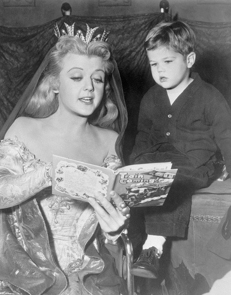 Looking like something out of a fairy tale, film star Angela Lansbury amuses a tiny visitor, her son, Michael, by reading a modern fairy tale during a break in Hollywood film work. Angela's dressed for her part in 'The Court Jester', comedy set in medieval times, which also stars Danny Kaye and Glynis Johns.