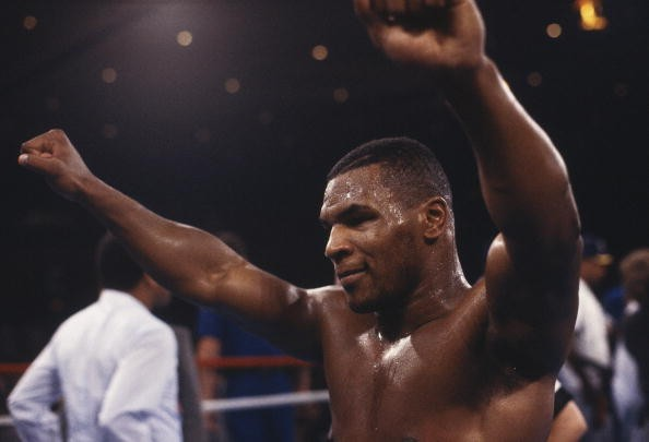 Mike Tyson raises his fists after winning a bout.