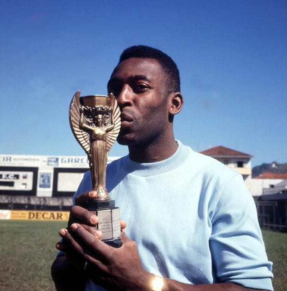 Football, Brazilian legend Pele, one of the stars of the victorious Brazil team of the 1970 World Cup Finals in Mexico, kisses the Jules Rimet trophy circa 1970.