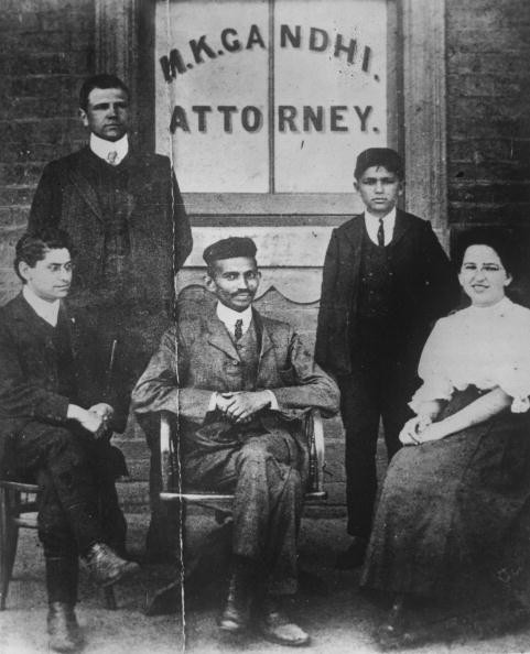 Mahatma Gandhi (Mohandas Karamchand Gandhi, 1869 - 1948) when he was practising as an attorney in South Africa. He is seated in front of a window bearing his name, on the left is H S L Polak then his clerk. The woman is Miss Schlesin, a Russian.