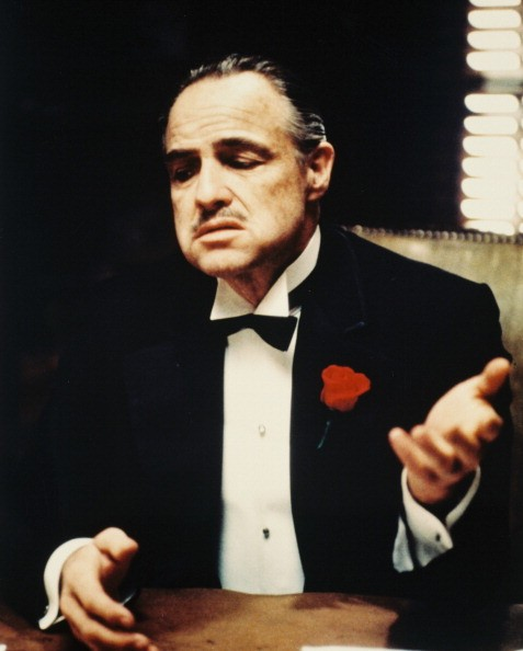 Marlon Brando (1924-2004), US actor, wearing a black dinner jacket with a white shirt and black bow tie, with a red flower on his lapel, in a publicity still issued for the film, 'The Godfather', 1972. The mafia drama, directed by Francis Ford Coppola, starred Brando as 'Don Vito Corleone'.