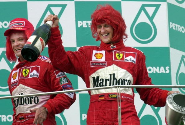 Wearing red wigs, Ferrari Formula One drivers world champion Germany's Michael Schumacher (R) and Brazil's Rubens Barrichello celebrate after finishing respectively first and third in the Malaysian Grand Prix 22 October 2000. Seven-times world champion Michael Schumacher of Germany will retire at the end of the current season, his Ferrari team announced after his victory at Monza here 10 September 2006.