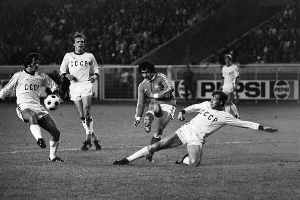 French soccer national team player Michel Platini (C) kicks the ball in spite of two Russian defenders, on October 08, 1977,at Paris, during the friendly match France vs. URSS.